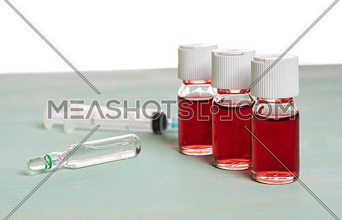 medical vaccine vials with red liquid and syringe over green table and white background. Vaccination and immunization conceptual.
