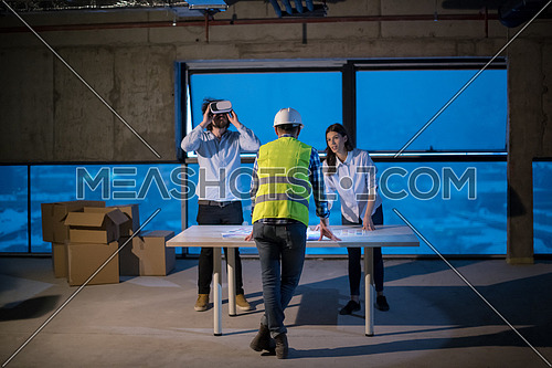 young team of business people in group, architect and engineer on construction site checking documents and business workflow using laptop computer in new startup office