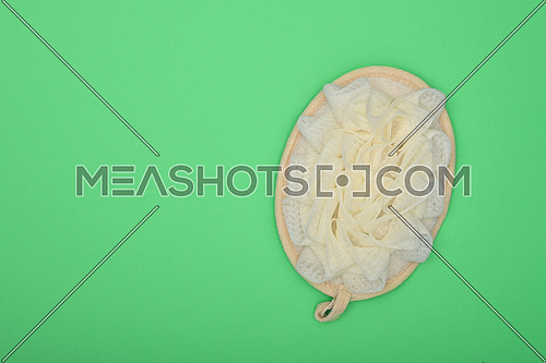 Close up one feminine soft bath shower skin scrub puff over green background, elevated top view, directly above