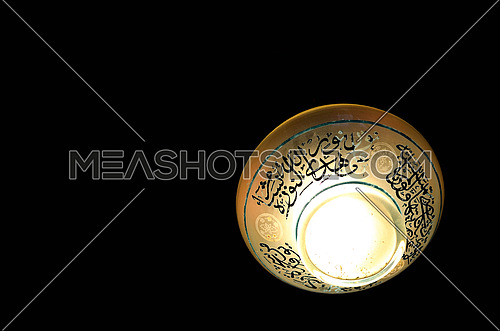 A ceiling lamp with islamic writings isolated on black