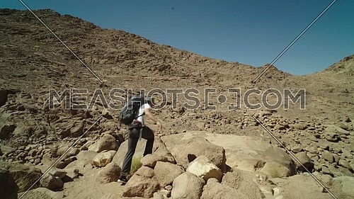 Follow shot for a male tourist wearing a pink cap and travel backpack explore Sinai Mountain for wadi Freij at day.