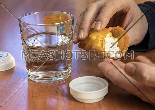 Hand spilling pills for the pain of a bottle