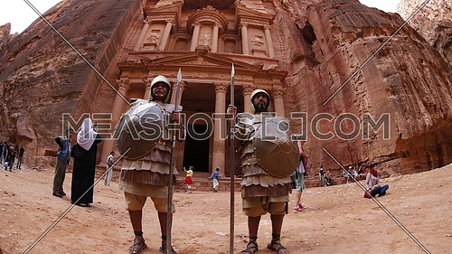 two men in traditional Nabatean clothes standing in front of petra