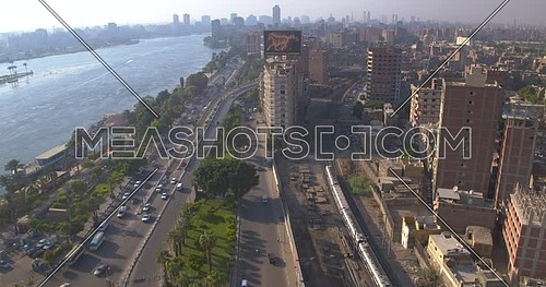 Reveal shot for the city beside the River Nile while Metro Passing by in Cairo at sunset