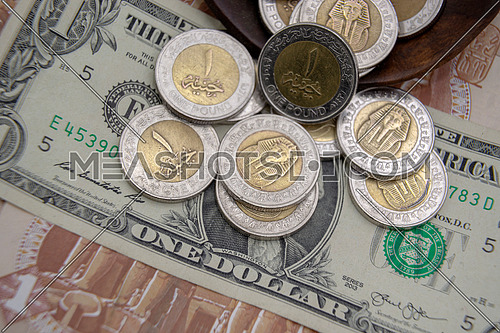 many pieces Egyptian 1 pound gold and silver metal coins dropping on paper note USA one dollar - banknote  background - currency value compare