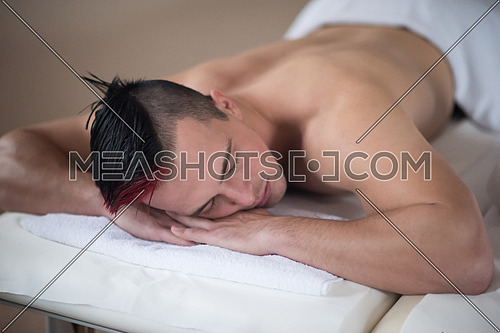 young handsome man have relaxing massage in spa and wellness salon
