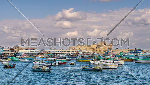 Old east harbor of Alexandria city at the Mediterranean Sea with fishing boats in the foreground and the Citadel of Qaitbay in the background in a cloudy winter day, Egypt