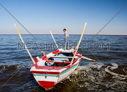 a boy standing on a boat