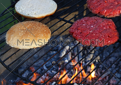 Close up raw beef meat burgers and sesame buns for hamburger cooked on fire barbecue grill with smoke and flame, high angle view