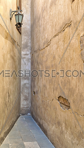 Dead end Narrowing isle with stone grunge walls and lantern at an old abandoned historic palace, Cairo, Egypt