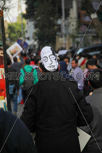 A man from his back wearing ahmed harara mask in a protest
