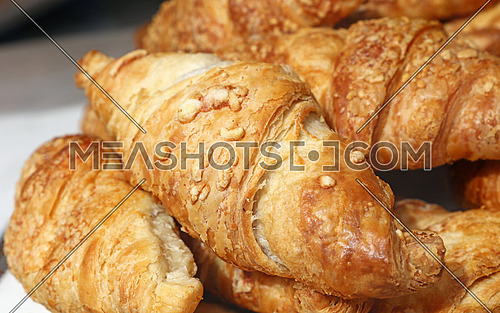 Freshly baked golden brown French croissants with cheese topping in retail bakery store display, close up, high angle view