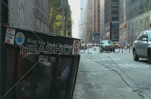 Close shot for Trash can on Street corner at New York City Showing Traffic, Cars at day
