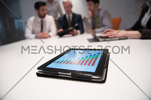 Close up of tablet touchpad computer with focus on business analytics and progress chart document. Business people group on meeting in background