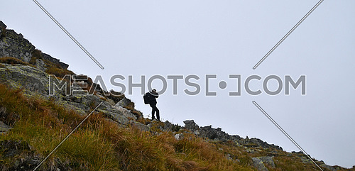 One tourist man photographer with backpack taking pictures in mountains on foggy weather day, low angle side view