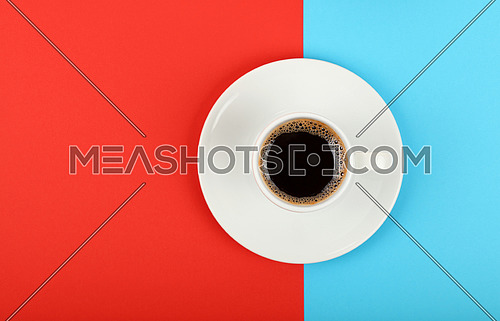 Close up one white cup full of black coffee on saucer over colorful red and blue background, elevated top view, directly above