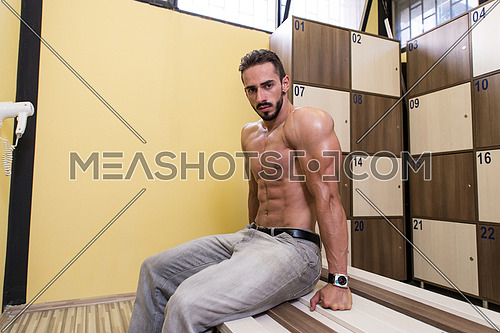 Muscular Build Athlete Sitting In Gym's Locker Room And Having A Rest After Workout