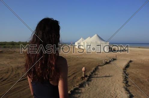 Follow shot for a girl walking in sand by sea at wadi lahmi at day - 5D
