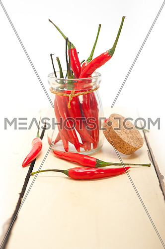 red chili peppers on a glass jar over white wood rustic table