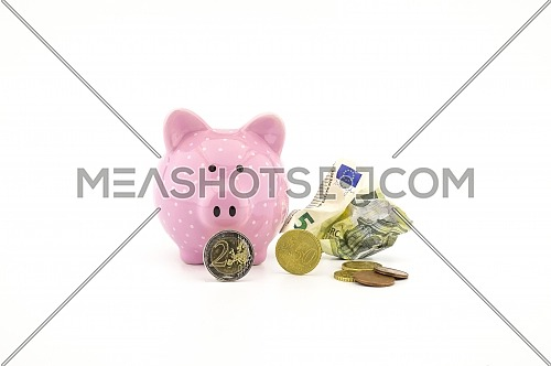 Crumpled banknotes, coins and cute pink piggy bank on white with copyspace for financial or savings concepts