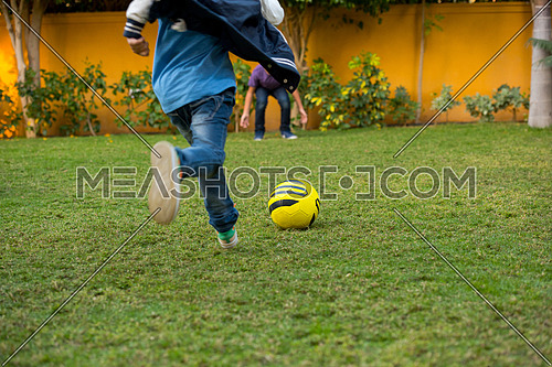 middle eastern boys kicking the ball in the yard and enjoy it
