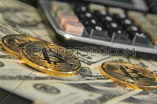 Closeup shot for Bitcoins and dollars with calculator in background