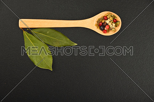 Group of bay two laurel leaves and mix of peppercorn in wooden spoon on black chalkboard background