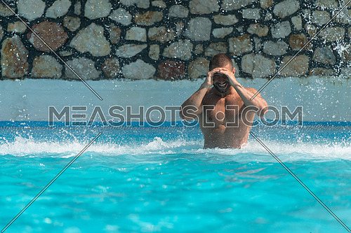 Man In A Public Swimming Pool Standing Under A Water