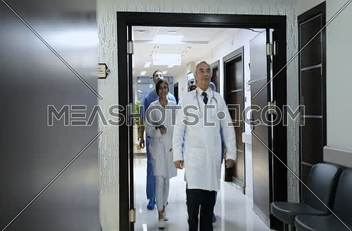 middle eastern doctor and his team walking forward in hospital corridor