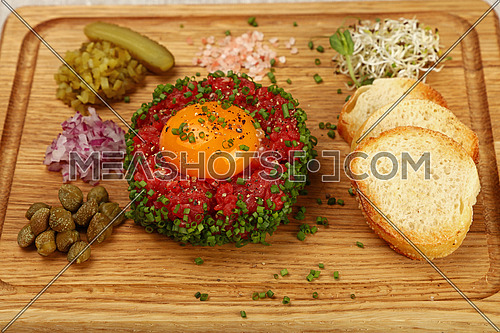 One portion of raw minced beef meat tartare steak with egg yolk, baguette bread, green chive, onions and capers on wooden board, close up, high angle view, personal perspective