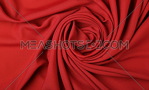 Close up abstract textile background of spiral shaped red folded pleats of fabric, elevated top view, directly above