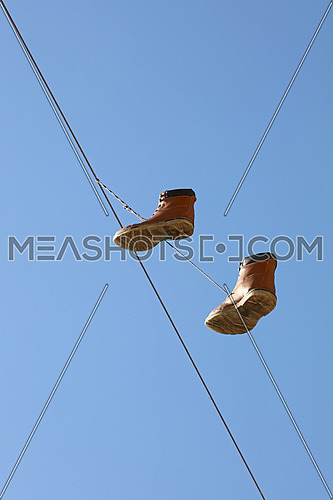 Pair of old worn brown boots hanging on a telephone line wire as traditional urban youth joke, over clear blue sky, low angle view