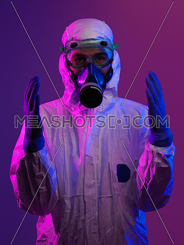 Doctor wearing protective biological suit and mask due to coronavirus 2019-nCoV global pandemic warning and danger background in blue and pink background.