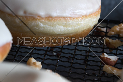 Side view of donuts with white glaze and nuts on a net