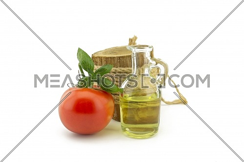Fresh cherry tomato and basil leaf and oil in decanter over a white background in a healthy diet and nutrition concept