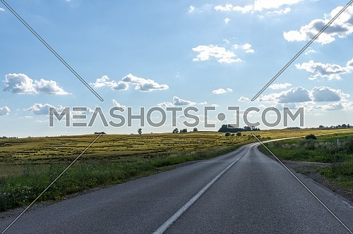 Deserted asphalt road winding away over a hill in the distance on a sunny spring or summer day with blue sky and clouds in a rural landscape