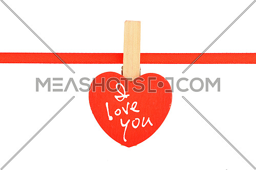 Red painted wooden heart with clothes pin on textile ribbon with I love you text message isolated on white background