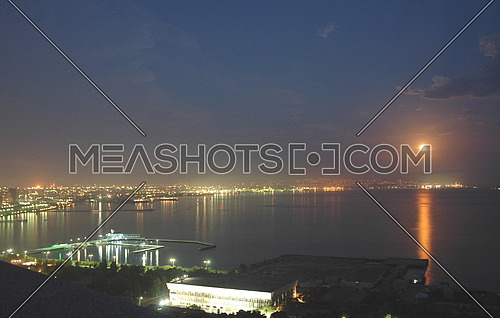 Baku city at night and reflection of moon in the water