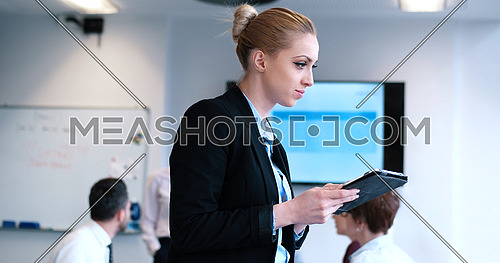 Portrait of  smiling casual businesswoman using tablet  with coworkers standing in background