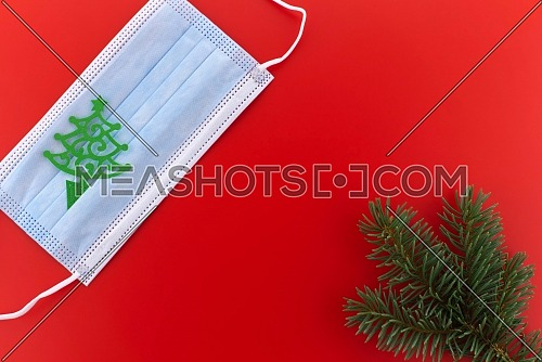 Face mask with paper cut Christmas tree over a red background with copyspace