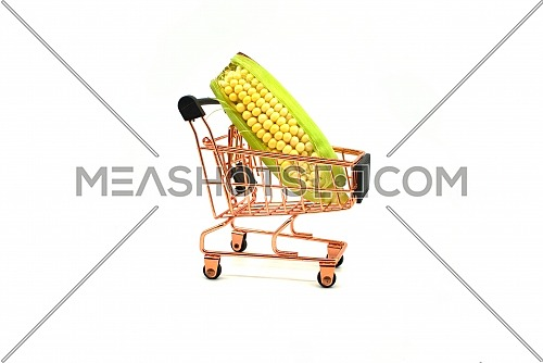 Fresh corn on the cob in a small shopping cart over a white background in a diet and nutrition concept