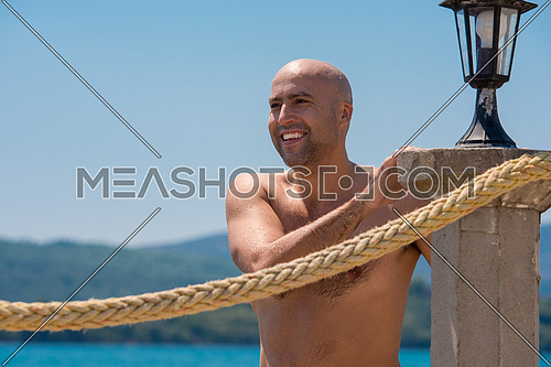Portrait of a young smiling muscular man with naked torso while standing on the coast by the sea