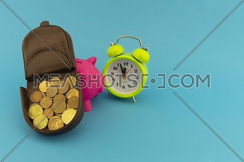 Saving and retirement concept with open purse with coins, alarm clock and piggy bank over a blue background with copy space