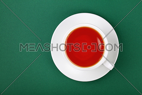 Close up one full white cup of black red tea on saucer on green table background, elevated top view, directly above