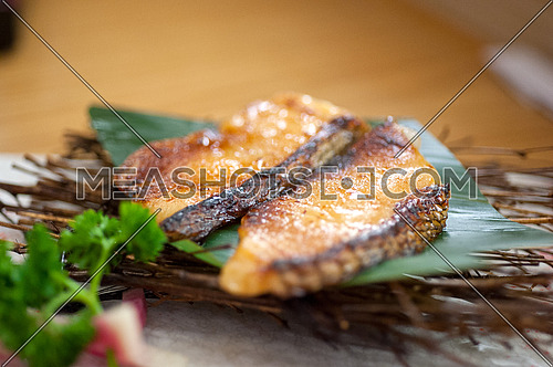 Japanese style teppanyaki roasted cod fish on palm leaf