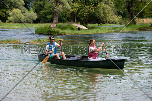 Couple friends are canoeing in a wild river surrounded by the  beautiful nature