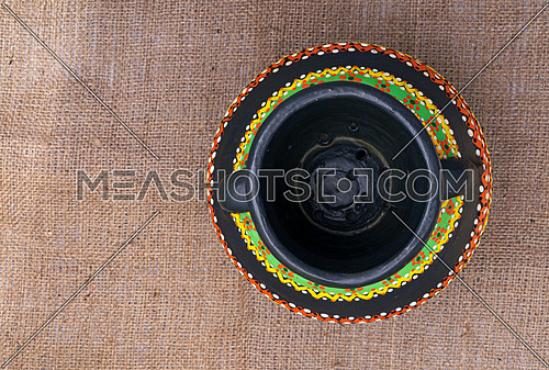 Top view of a black Egyptian handcrafted artistic pottery jar on a sackcloth background