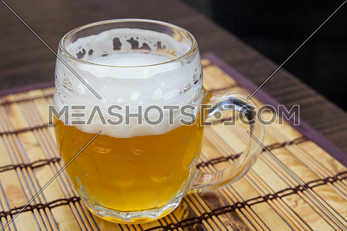 One glass mug of unfiltered craft draft white wheat weizen beer on wooden bamboo mat on table, close up