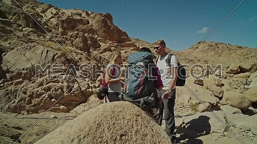 Follow shot for a group of tourists wearing backpacks standing and talking while exploring Sinai Mountain for wadi Freij at day.