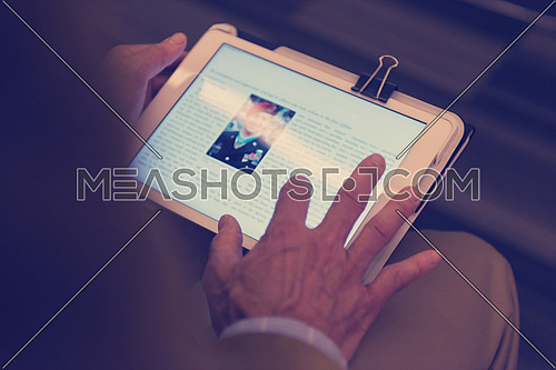 Closeup of mature hands holding tablet. Teacher with students in classroom